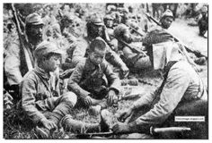 A Japanese soldiers talks to very young Chinese boy soldiers