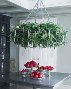 Holiday Wreath Chandelier. When suspended from the ceiling, this impressive, ornament-laden ring of greens will thrill your guests. Its wild, earthy look comes from the tangle of lichen branches and seeded eucalyptus, which are simply tucked into noble fir wreaths. The pomegranates below are brushed with edible luster dust, adding to the glow of the red-and-green tableau.