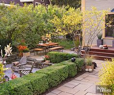 Multiple levels featuring different flooring materials help define this outdoor space's different zones. Three steps down from the wooden deck, a stone patio offers plenty of space for dining. Two more steps down, a gravel-surfaced area surrounded by a short stone wall offers a cozy place to sit and visit.
