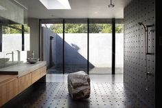 Heavy Metal (named for perforated metal screens cladding the house), by Hufft Projects LLC, has the beautiful bath. Great combination of dark shower wall/floor with freestanding rock and light wood millwork