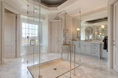Luxury spa like master bath with glass shower and double marble vanities