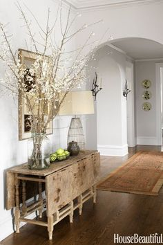 Beautiful neutral home design featuring pale gray walls, bright white trim, medium tone hardwood floors, a rustic antique drop leaf side table, a large arrangement of blooming branches, open wire lamp and a framed mirror - Modern Rustic Home Decor & Ideas