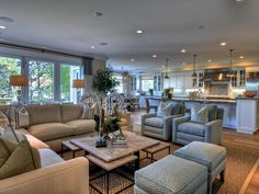Beach decor is found in the details in this spacious family room. Nautical art pieces, natural fabrics and warm tones of tan and sea blue come together to create a space to relax and unwind.