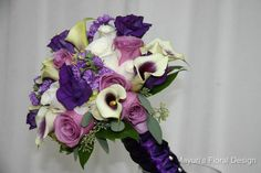 Pink, white and purple roses, white & purple calla lilies, with some green leaves.