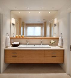 A floating wood bathroom vanity with a ceramic sink is below a large square  mirror. The contemporary vanity is also home to a small vase filled with  white ...