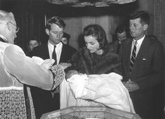 Her aunt Caroline Lee Canfield holds sixteen-day-old Caroline Bouvier Kennedy during her christening at St. Patrick's Cathedral in New York City, December 1957. Boston's Archbishop Richard Cushing officiates as the child's father, Massachusetts Senator John F. Kennedy, and her godfather, Robert F. Kennedy, look on.