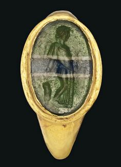 A ROMAN GOLD AND GLASS RING   CIRCA 1ST CENTURY B.C.-1ST CENTURY A.D.   The hollow rounded hoop widening to the shoulders and a stepped oval bezel set with an oval banded green, white and blue glass intaglio with a standing draped maenad with thrysus  1 in. (2.5 cm.) wide