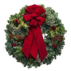 Fresh Christmas wreath with blue and yellow berries and a red velvet bow