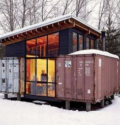 """Two twenty foot shipping containers were purchases at $800 each to create a cabin complete with kitchen, dining room, living room with a wood burning stove, laundry room and two queen beds. The two cabins are connected by a middle section loft and roof made out of """"(3) 4 1/2"""" X 11 1/4"""" fir beams made up of (3) 2X12's thru bolted and glued"""" and a glass door entrance."""
