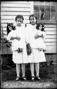Here's a striking image of two girls – definitely sisters, possibly twins – holding their beautiful and large bisque dolls!  The dolls look very much like the Schoenau and Hoffmeister mold 5500 doll