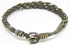 This is a superb ancient Viking braided silver bracelet / Oath-ring, dating to the 9th - 10th century A.D. It is formed from rods of silver, twisted about each other in a ropework formation, the terminals welded, forming a double spiral decorative element. This type of double spiral can be found on other Viking silver bracelets from Gotland in Sweden see here. This example recovered during dredging work is intact