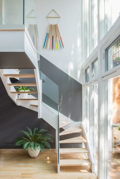 The back staircase abuts a glass facade overlooking the backyard and allowing plenty of light into the kitchen area above. The art hanging on the wall is by artist Julie Thevenot. Photo by Andrew Cammarano.  Photo by Andrew Cammarano.