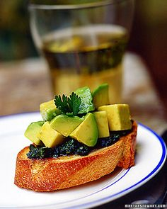 Blend parsley, basil, garlic, and red-wine vinegar with olive oil to make the brilliant green herb sauce for this bruschetta.  Spoon diced avocado on tip just before serving.