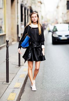 White button-down, black lightweight sweater, black leather circle skirt, and sneakers