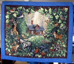 "A spectacular forest scene with a rustic cabin surrounded by a variety of forest animals.  This a beautiful quilt measuring 45"" x 38""."