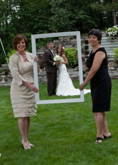 Moms in wedding photos, frame the couple. Love the idea of having mom hold the frame