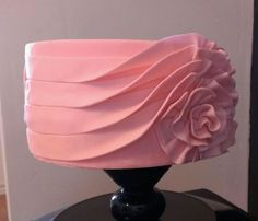 looks like a Valentino creation. 4 strips of fondant along side of cake, ruffle one end and form rosette, covers beginning of the fondant strips