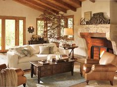 American Classic Living Room   This inviting and visually restful space begins with walls painted a warm ivory, which makes the entire room seem awash in a soft glow. The ivory upholstered sofa, soft caramel-leather armchair and pale porcelain-blue rug keeps the room looking not only well-designed and stylish, but create a compelling space for relaxing and entertaining.