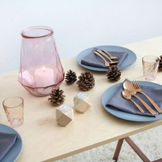 Table Decoration with copper cutlery, pine cones and tinted glass.