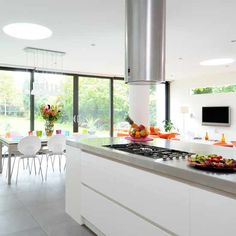 Open-plan kitchen diner. I  like the white and the cabinets under the hob. Oven extractor fan is a bit big though.