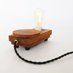 Lamp 'Disc small'.  This lamp is handcrafted in small series of oiled Iroko wood. The horizontal disc operates the dimmer and switches the lamp on/off. #lamp #tablelamp #light #illumination #warm #retro #edison #filament #fabricwrappedcord #woodwork #wood #design #lighting #brass #ceramic #porcelain #dimmer #artdeco #deco #vintage #authentic #disc #oiled #tungoil #rubber #Zzz #handmade #handcrafted #upcycling #object #hip #exclusive #iroko #ST48 #unique
