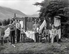"New Zealand circa 1905. ""Men doing chores at a campsite, all in striped tops, poss­ibly Sumner, Christchurch."" Glass negative by Adam Maclay."
