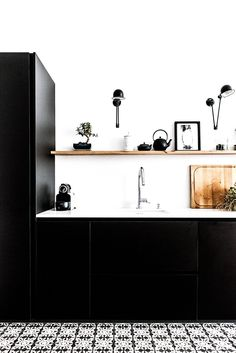 Black kitchen inside of bohemian paris apartment