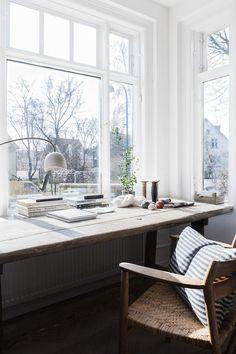Scaffolding plank desk beside a bright window.
