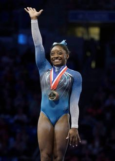 Simone Biles waves after being named overall winner in the U.S. women's gymnastics championships Sunday, June 26, 2016, in St. Louis.