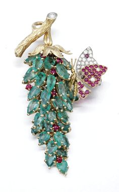 Emerald, ruby and diamond brooch, Marchak, 1950s Of floral design set with pear-shaped emeralds, cabochon rubies and brilliant-cut diamonds, enhanced with a ruby and diamond butterfly, signed Marchak and numbered 23.960, French assay and maker's marks, length approximately 75mm.
