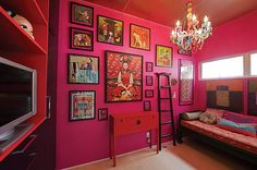 A pink or red wall with black framed asian art - love the ladder and the chandelier too