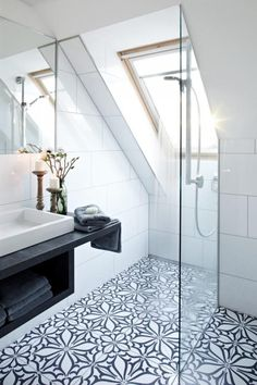 This loft bathroom has all the trademarks of Scandinavian style, with large white tiling, but they have made it much more unexpected with these patterned floor tiles and the dark basin unit.