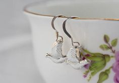 Small silver birds are flying through the sky with their wings raised high.   These delicate birds are attached to light hooks to create a vision of the birds in motion as they sit just below the earlobe.