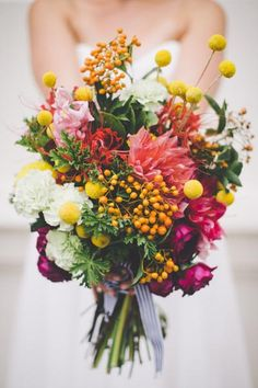 Billy balls add a colorful accent to this rustic wedding bouquet.