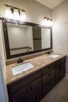 Beautiful master bathroom with two sinks. Dark cabinets and trim around the mirror.