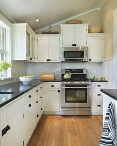 source: Union Studio Architects Kitchen with light gray sloped beadboard ceiling, khaki colored walls, white kitchen cabinets with black honed countertops and glossy white subway tile backsplash. Kitchen features microwave installed above stainless steel stove.