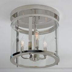 "Sleek Cylinder Modern Ceiling Light This clear paneled cylindrical flush mount is a show case modern fixture. Available in Polished Nickel or Satin Nickel with clear glass. 3x60 watts candelabra base bulbs. (14""Hx12.5""W)"