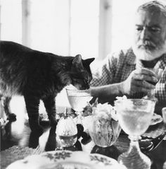 Ernest Hemingway at table with his cat Cristobal.  - John F. Kennedy Presidential Library & Museum