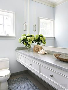 Whether granite, limestone, or marble, stone countertops take the chill off a bathroom's bright-white fittings. Here, a stone countertop draws the eye down the length of a floating vanity; the earthen surface connects to stonework on the floor for a pleasing visual connection.  /