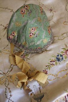 Fitted ladys cap, second half 18th century, green silk brocade with silver lace trim and original yellow silk ribbon ties. French in origin. Hand loomed linen lined. Of course entirely hand stitched. The silk ribbon has special scalloped detail at edges.