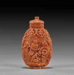 Carved coral snuff bottle; of ovoid form: the front with design of a bird on flowering branch with finely detailed blossoms; verso with pine and rockery; the coral of lovely pink-toned salmon coloration, with matching stopper