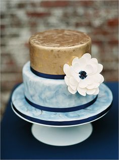 gold and blue wedding cake with a Dahlia Sugarflower