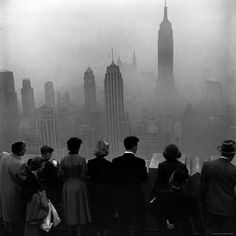 Several people standing on the top of a building looking down into the downtown misty smog that is covering the Empire State & surrounding buildings, New York, November 1953 (LIFE Magazine). Photograph by Eliot Elisofon . Photos Du, Old Photos, New York City, A New York Minute, Voyage New York, Black And White City, Night Pictures, Old Photography, Vintage Photographs