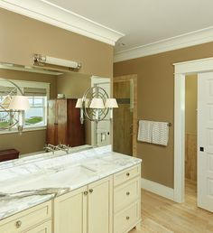 Stunning bathroom with light hardwood floors and toffee colored walls with crisp white trim.