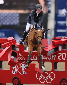 Scott Brash of Great Britain on Ursula XII piles through the London 2012 bus during the Longines Global Champions Tour of London on Day Four at Olympic Park on June 9, 2013 in London, England. (Photo by Mike Hewitt/Getty Images)
