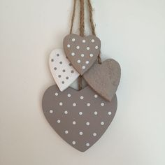 These wooden hanging hearts by Gisela Graham are attached to natural rope for hanging up There are four different size hearts some with dots in taupe