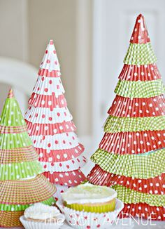All you need is 12×12 Cardstock, Cupcake Liners, and Tape.  Make the cones with cardstock.  Tape the ends well so the cones hold their shape.   Cut the center of your cupcake liners.  All you want is the ruffle part…  After you are done start taping the ruffles from the bottom to the top.  Use multiple ruffles.  Before you reach the top cover the tip of the tree with one of the centers of the liners.  After it is taped and secured finish the last ruffle layer… Ta Da!  Finished!