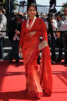 "Vidya Balan at ""Un Chateau En Italie"" premiere at Cannes Film Festival 2013. She is wearing again Sabyasachi red floral Saree with pearl jewellery & a white Ferragamo handbag."