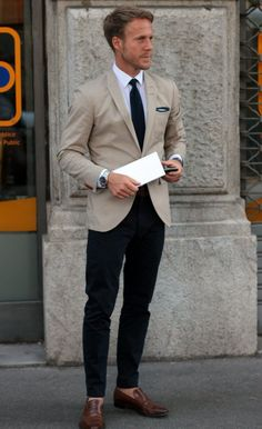 Tan blazer, navy pants, blue tie, white shirt.