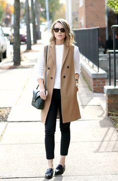 camel longline vest, white cble sweater, black pants, shoes and bag outfit